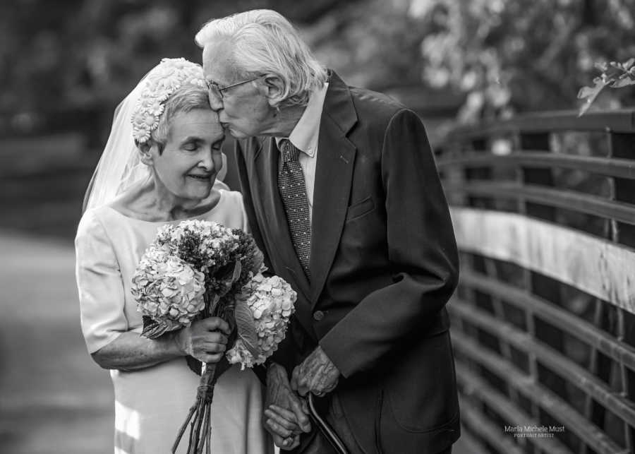 Elderly couple walk hand-in-hand while the husband kisses his wife on the forehead