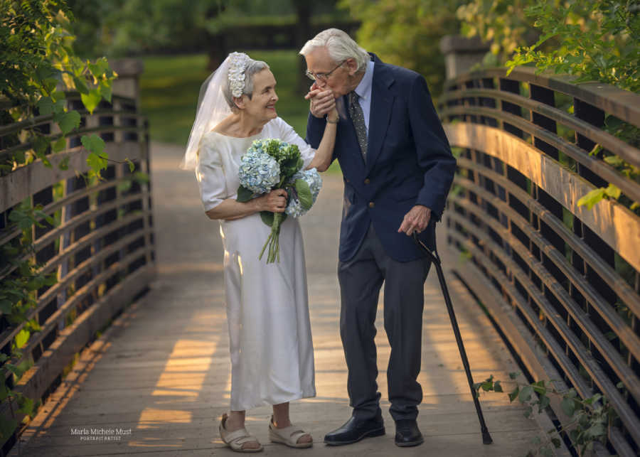 Elderly man walks with a cane and kisses his wife's hand on their 50th anniversary