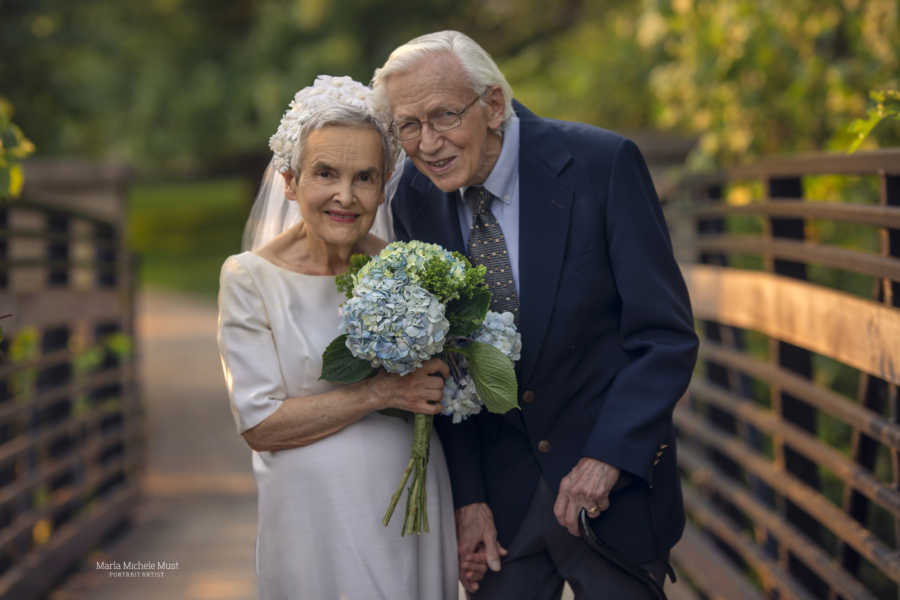 Elderly couple celebrating their 50th wedding anniversary wear their original wedding outfits during a photoshoot