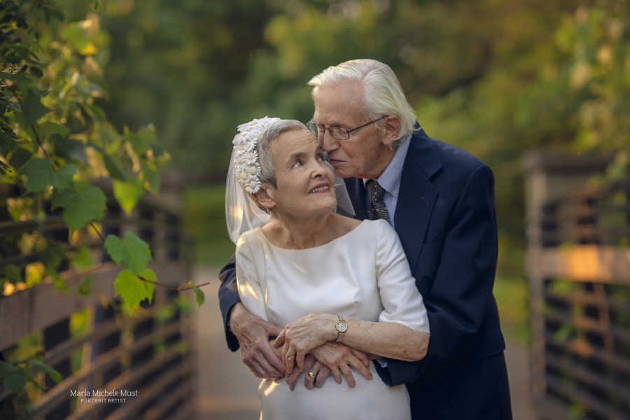 Elderly couple celebrating their 50th wedding anniversary wear their original wedding outfits and share an intimate hug