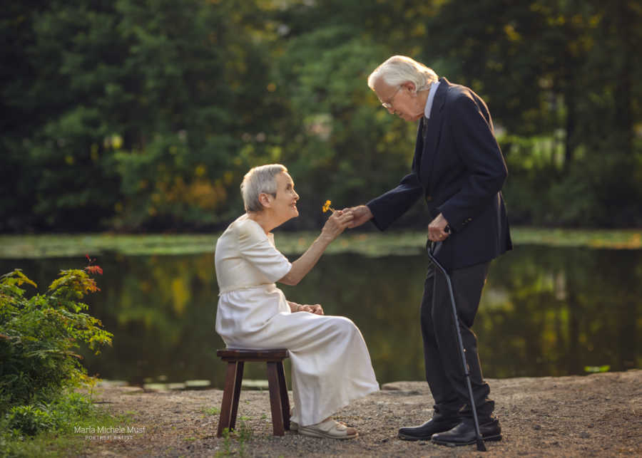Elderly man gifts his wife of 50 years a flower during their wedding anniversary photoshoot