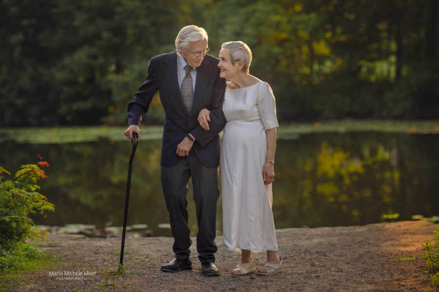 Elderly couple celebrating their 50th wedding anniversary walk arm-in-arm next to a lake, him in a blue suit and her in her original wedding dress