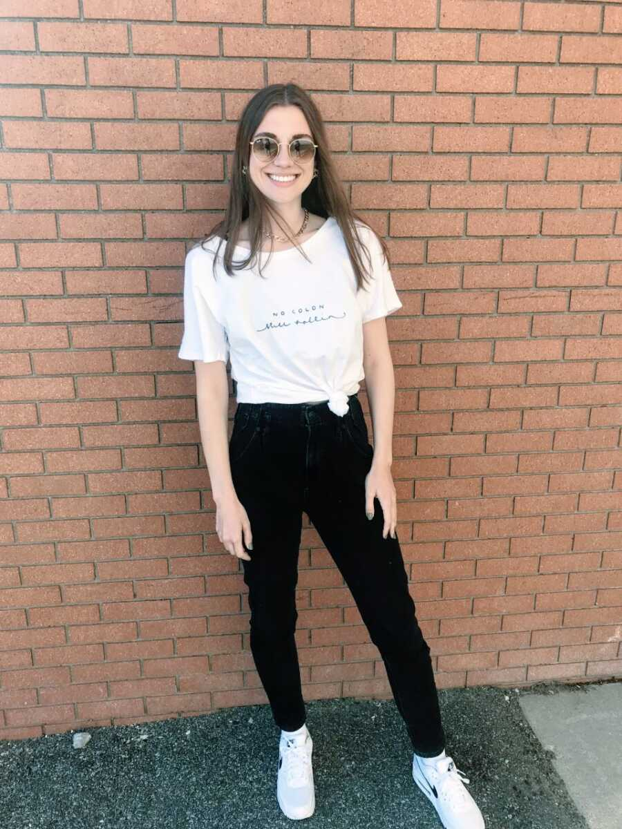 """Young woman who had a colectomy due to ulcerative colitis takes a photo wearing a shirt that says """"No colon, still rollin'"""""""