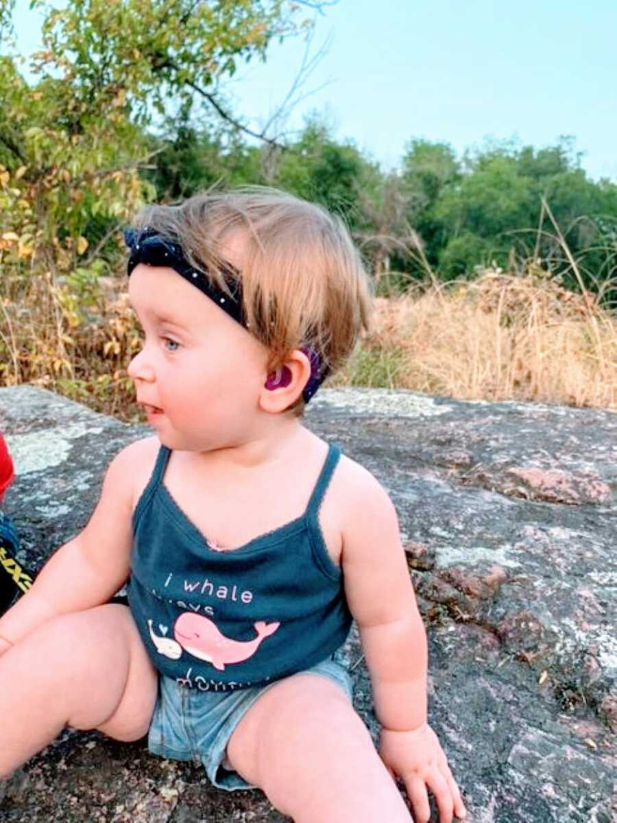 Little girl with hydrocephalus and deafness sits on a rock outside with hearing aids in