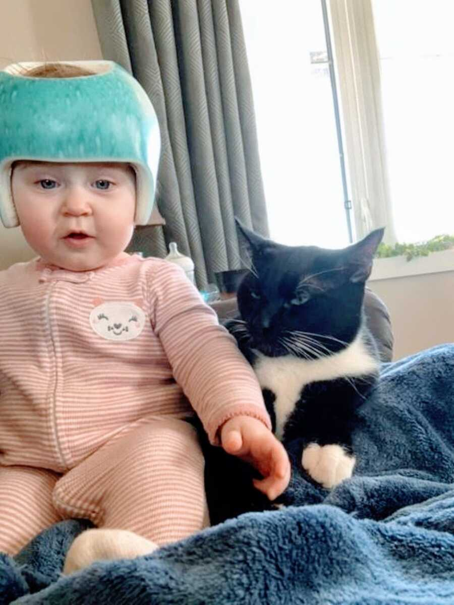 Little girl with hydrocephalus and torticollis wears a cranial helmet while sitting next to her family cat