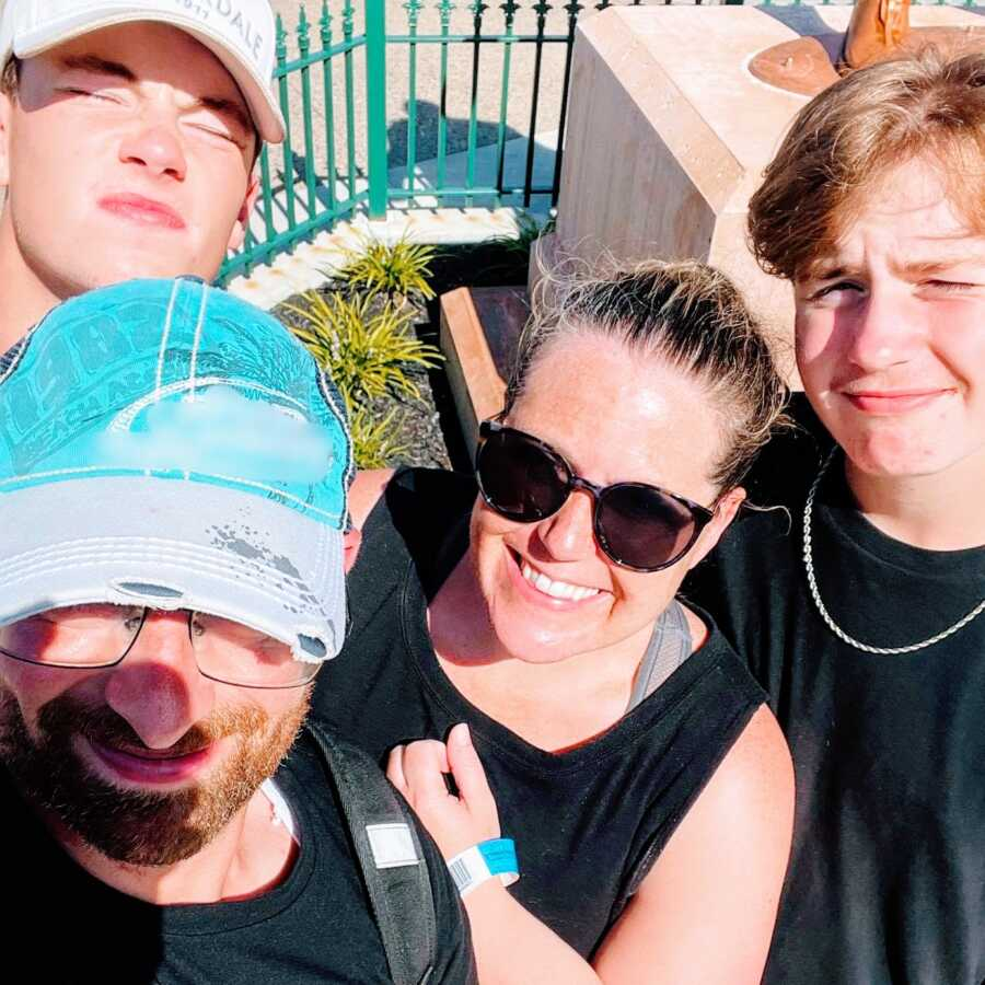 Mom smiles big in a family selfie while waiting in line for a thrill ride at an amusement park