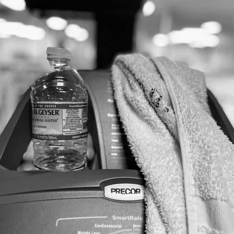 Woman snaps photo of her water bottle and sweat towel while working out at the gym