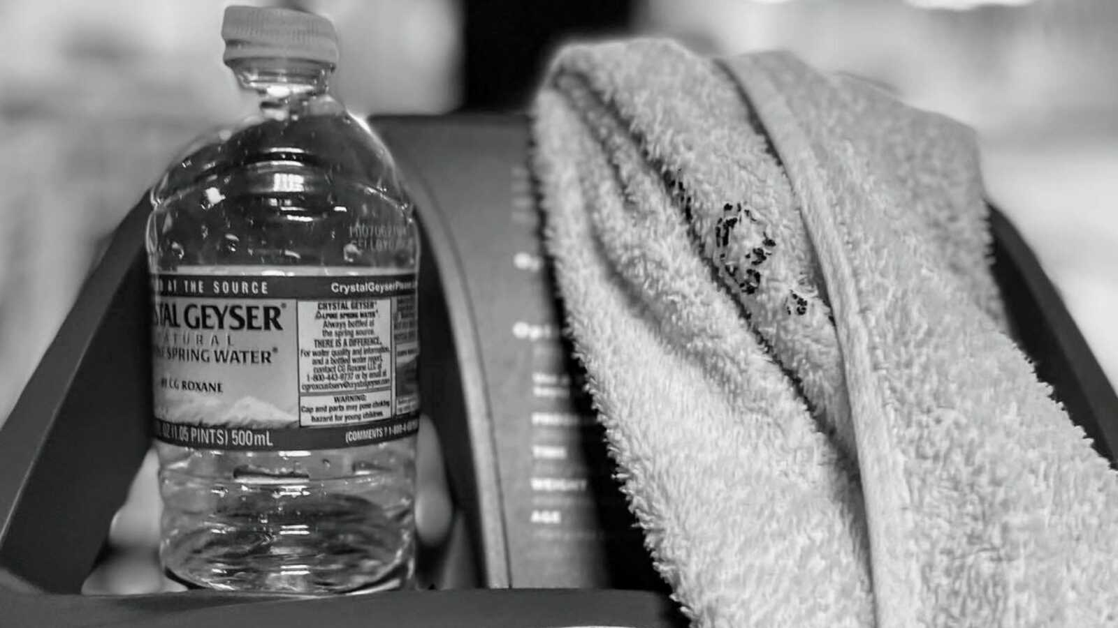Woman and mom of 2 learning self love takes a photo of her water bottle and sweat rag sitting on a treadmill