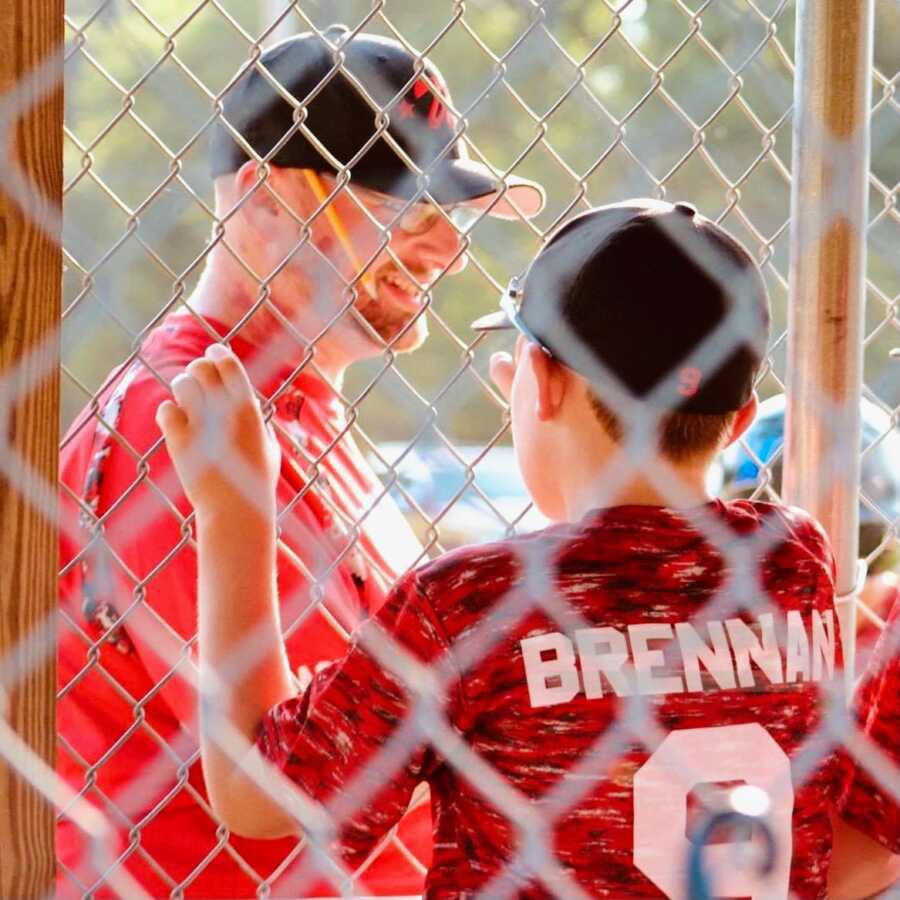 Dad coach looks at his son and his teammates and smiles during a baseball game