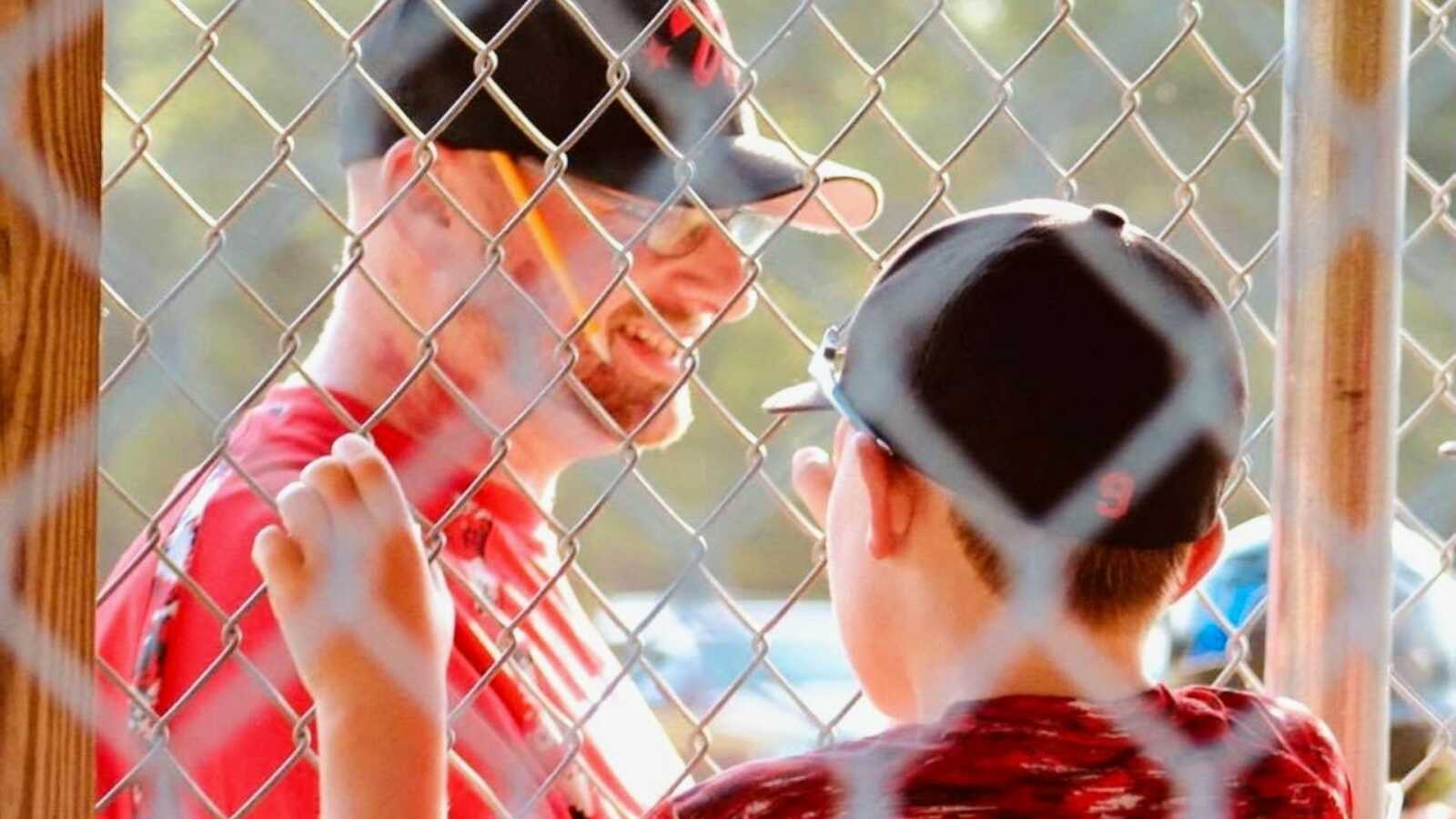 Dad and baseball coach smiles at his son and his teammates during a game