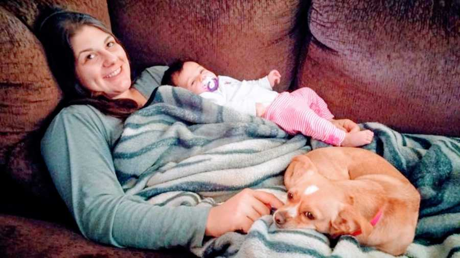 Young mom lays on a brown couch with her newborn daughter and her small brown dog