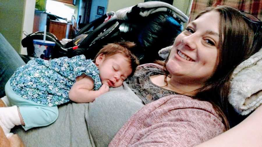 Mom of three takes photo of her newborn daughter curled up on her chest and sleeping in a blue outfit