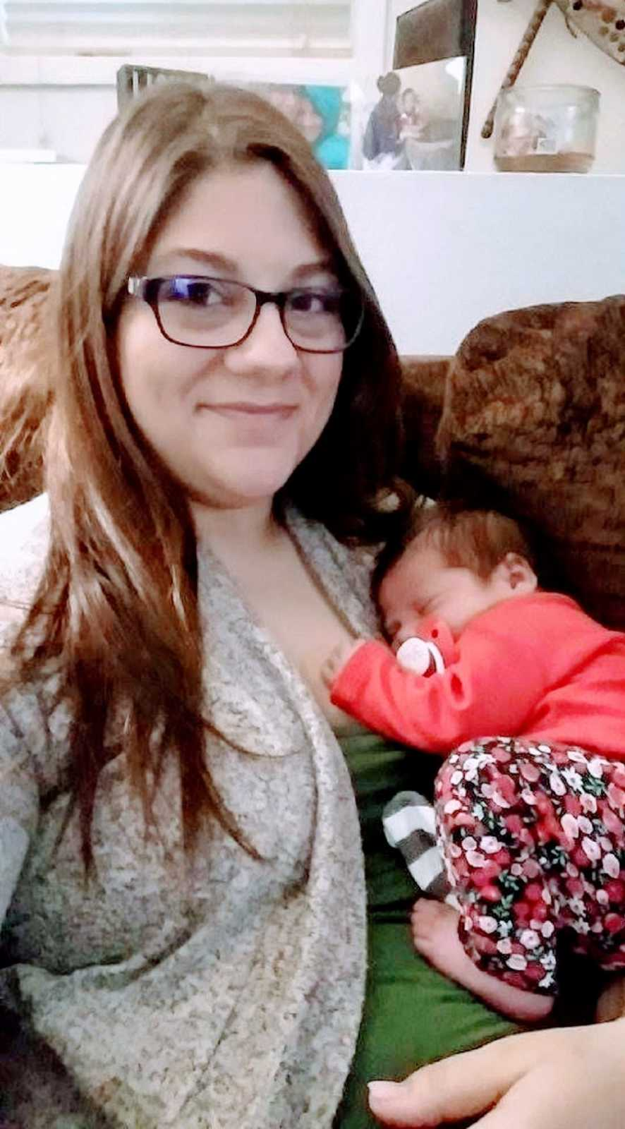 Girl mom takes selfie of her newborn daughter curled up sleeping on her chest