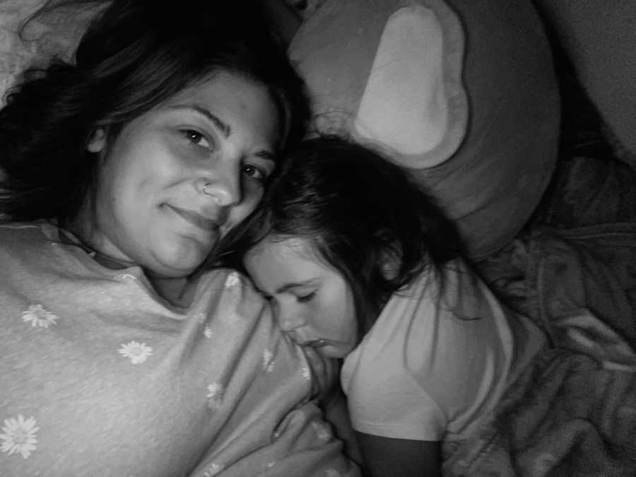 Mom and daughter snuggle together in bed after daughter grows too big to lay on her moms chest