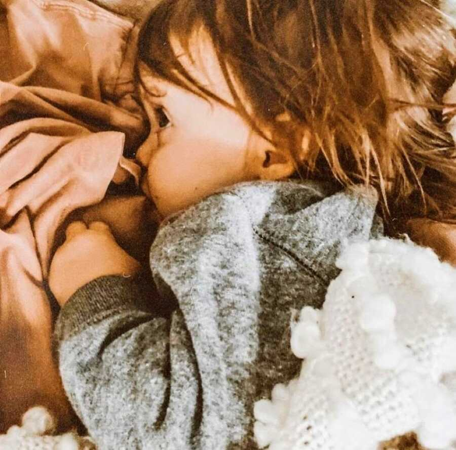 Little toddler with wavy brown hair cuddles up to their mom while breastfeeding