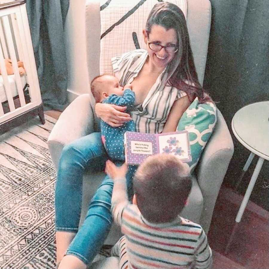 Mom breastfeeds her newborn in their nursery while reading her toddler a book