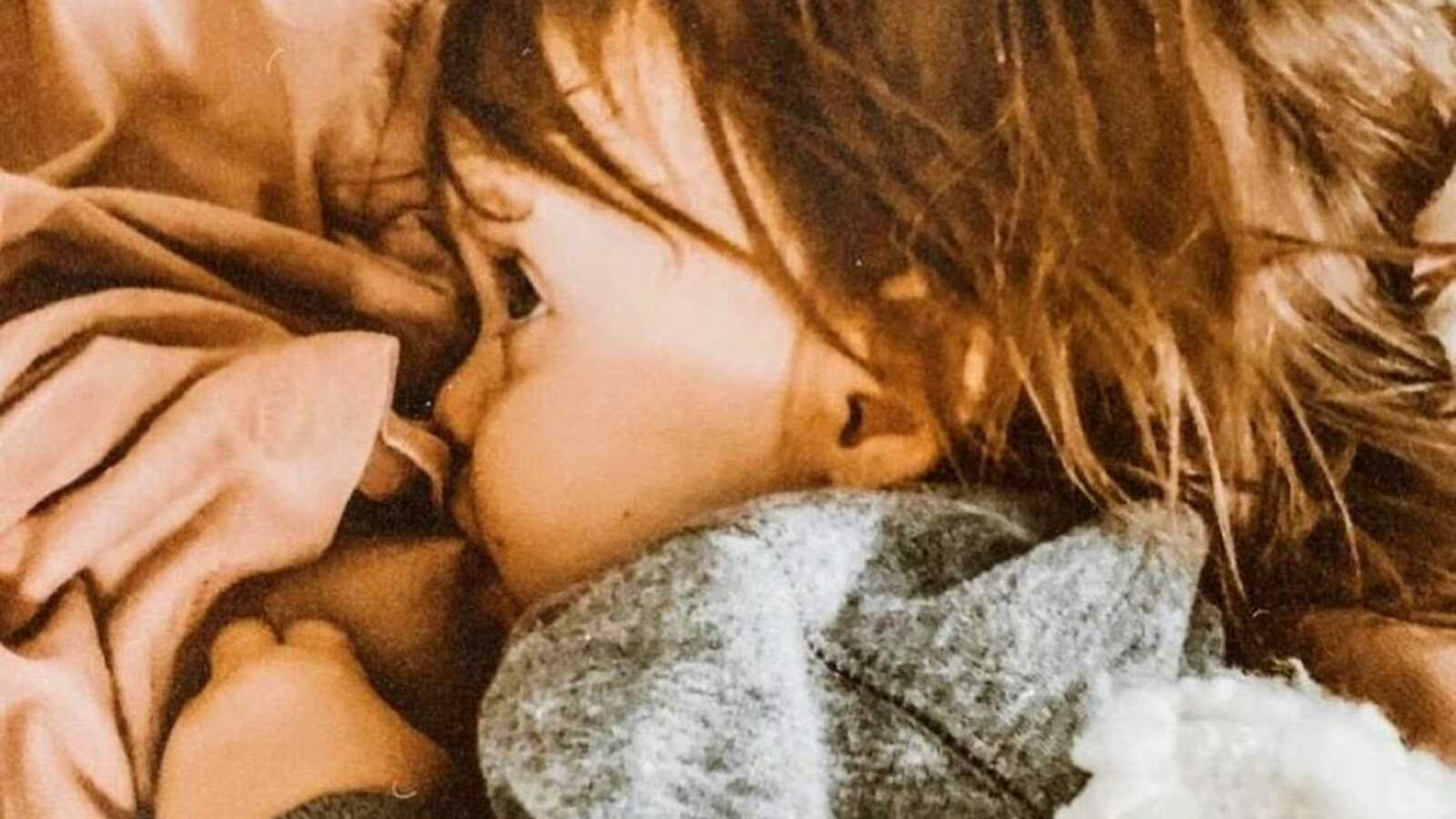 Mom takes photo of her toddler cuddling her while breastfeeding