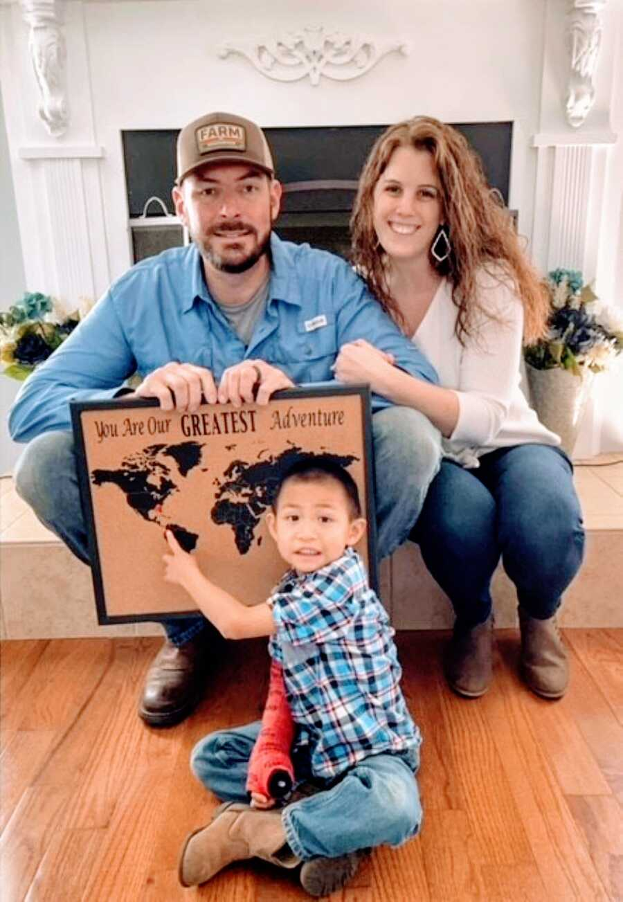 """Couple pose with their adopted son and a sign that says """"You are our greatest adventure"""""""