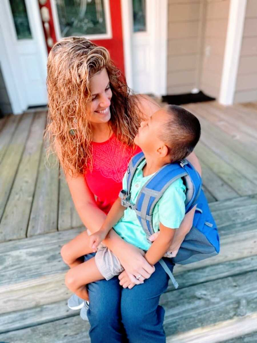 Mom and adopted son smile at each other while he sits on her lap with a backpack on before his first day of school