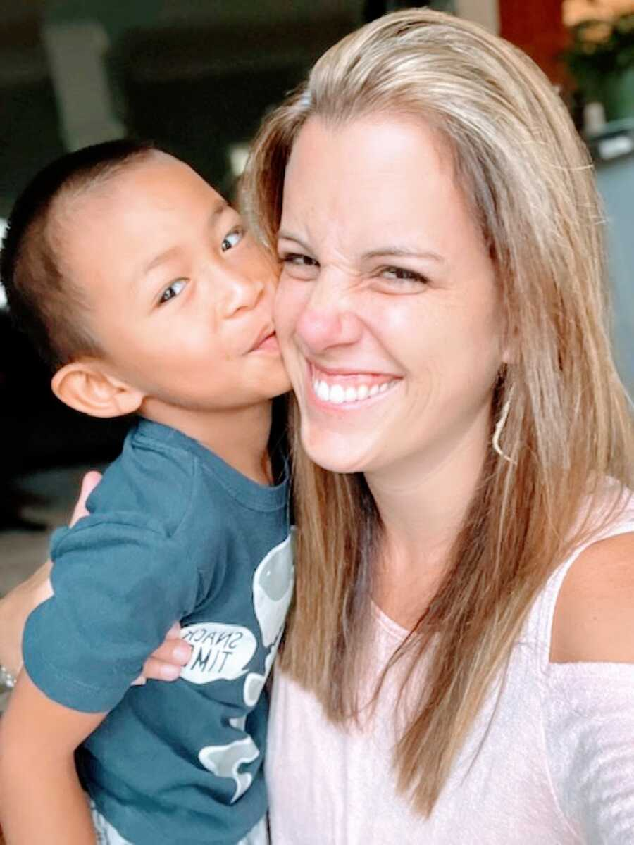 Adoptive mom smiles big while her adopted son kisses her on the cheek