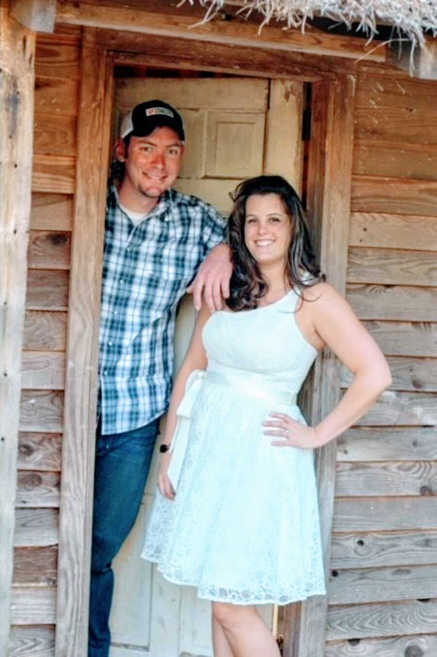 Recently married couple take photos together, the woman in a white dress and the man in a blue and green plaid shirt