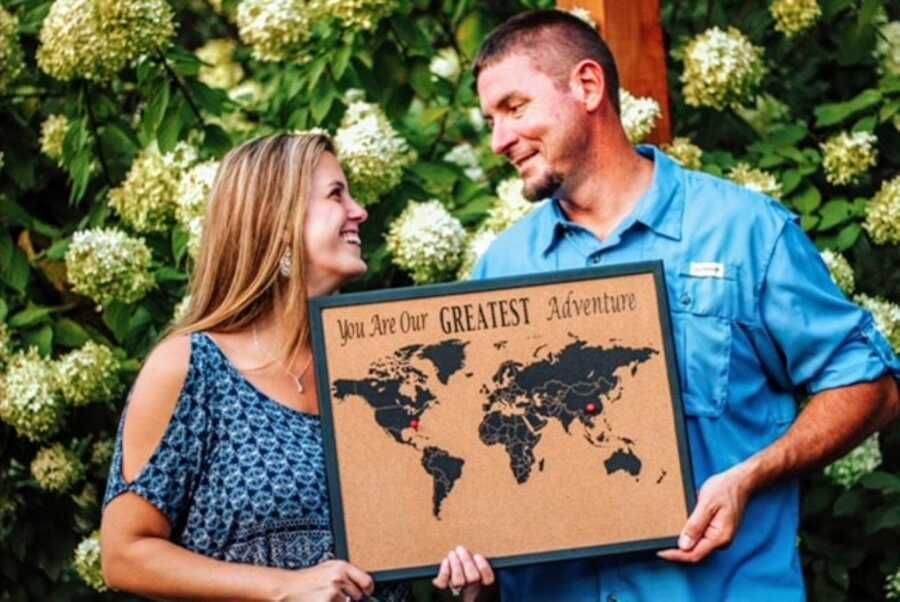 """Couple announce they are adopting a son from China with a sign that reads """"You are our greatest adventure"""""""