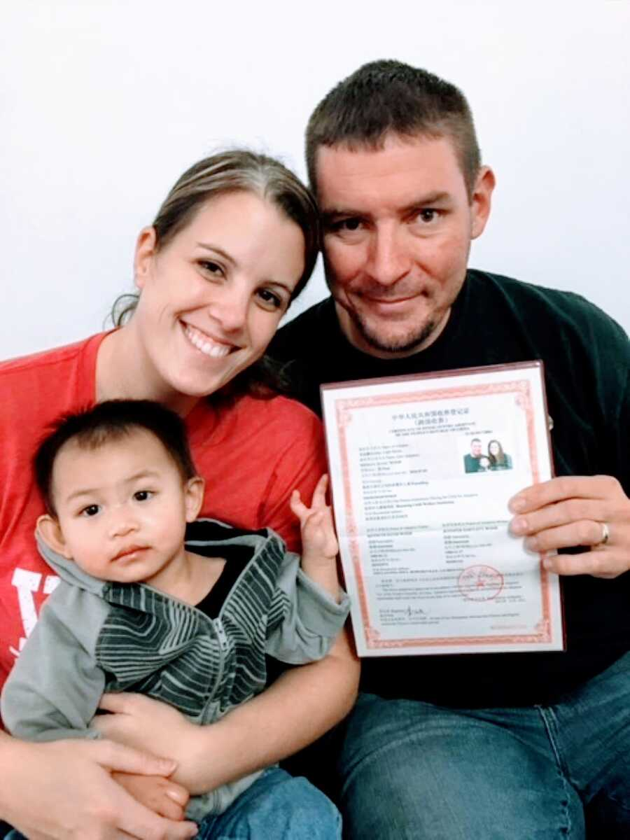 Married couple pose with their adopted son from China along with their official adoption papers