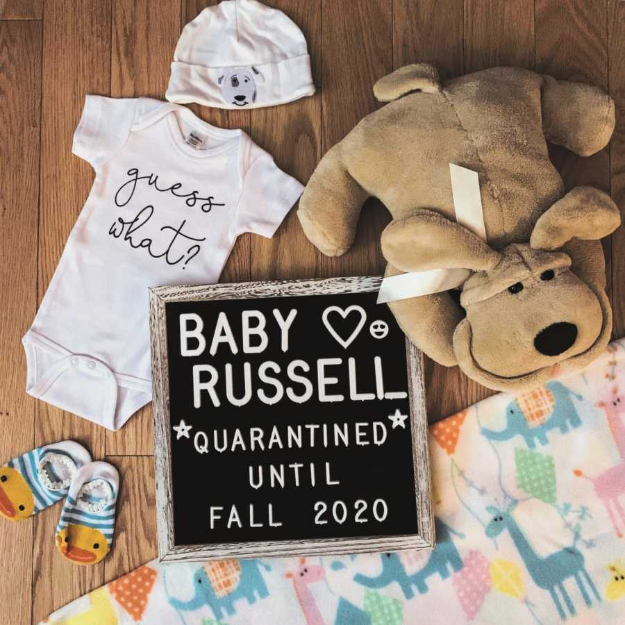 Expecting parents take pregnancy announcement photos with baby clothes and toys and a sign