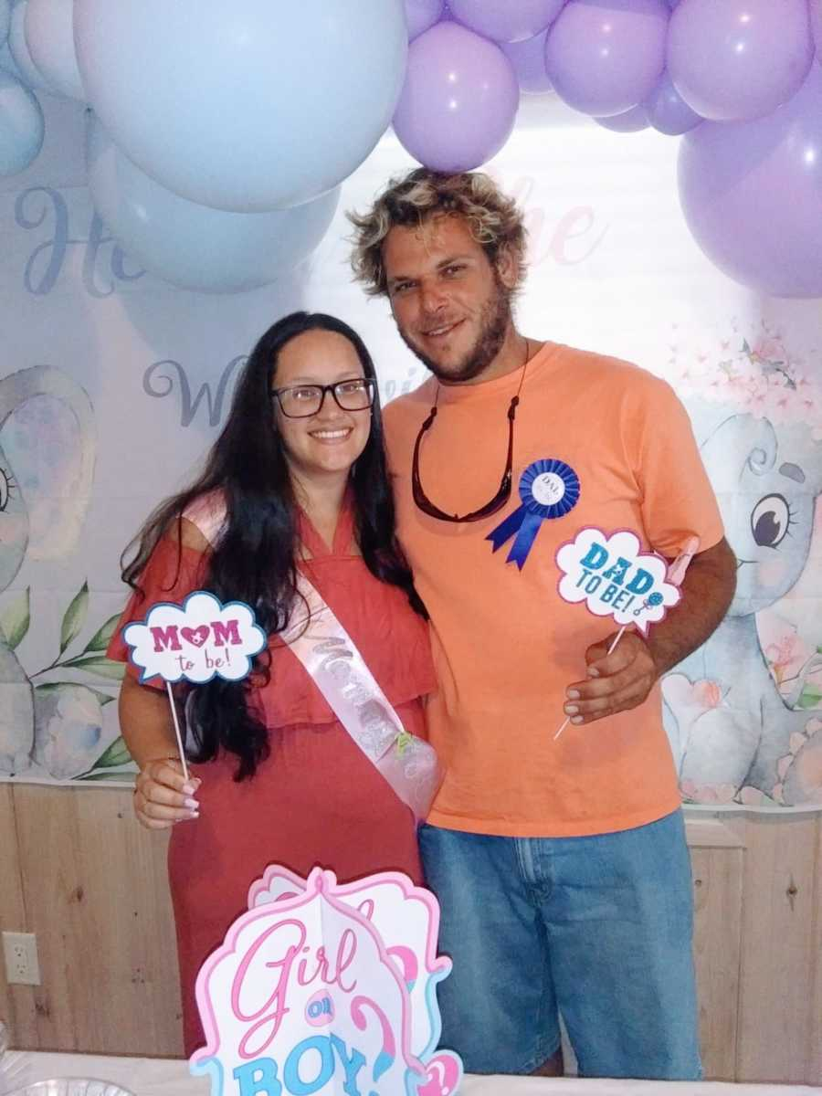 Young couple expecting their first child together take a photo at their gender reveal party
