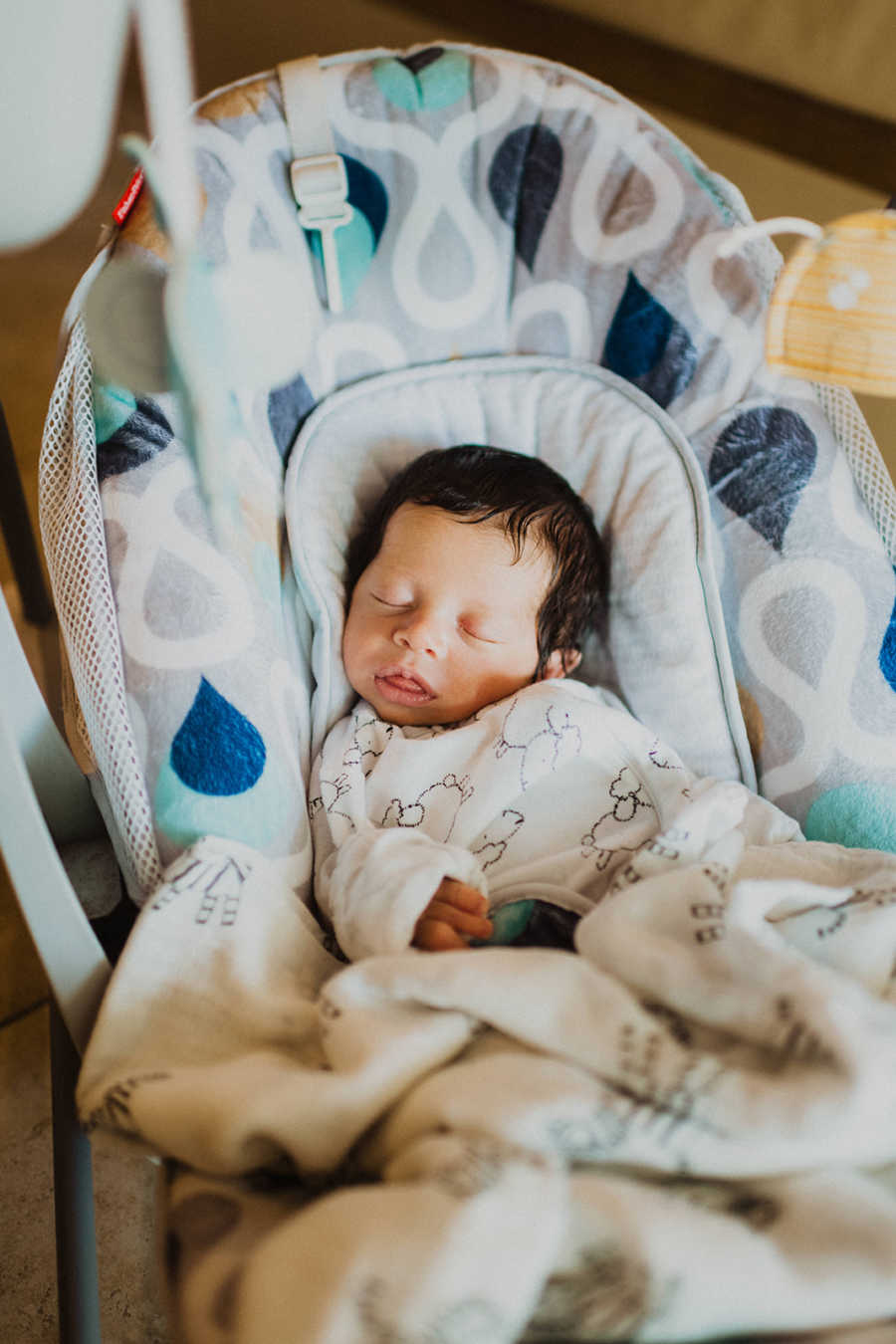 Mom snaps a photo of her son born with a limb difference sleeping in a baby carrier