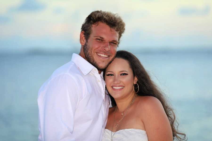 Young couple take maternity photos while wearing white on the beach at sunset