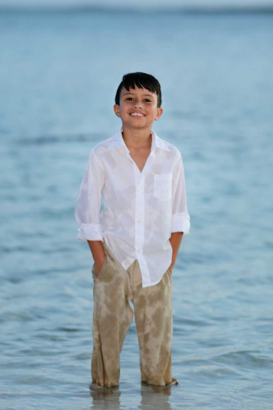 Young boy with epilepsy smiles on the beach during a family photoshoot