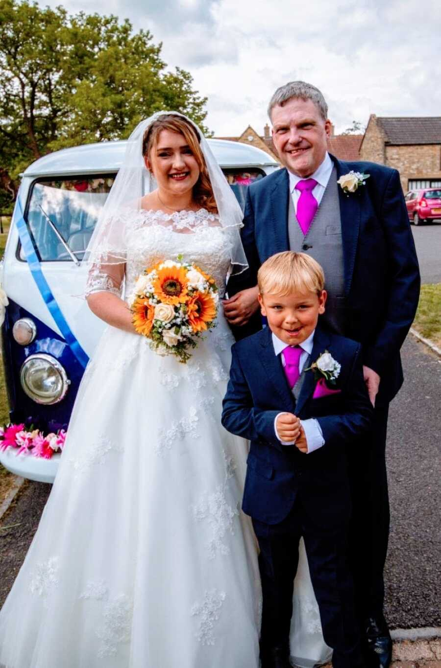 Young girl takes a photo with her dad while standing in front of a Volkswagen Bus on her wedding day