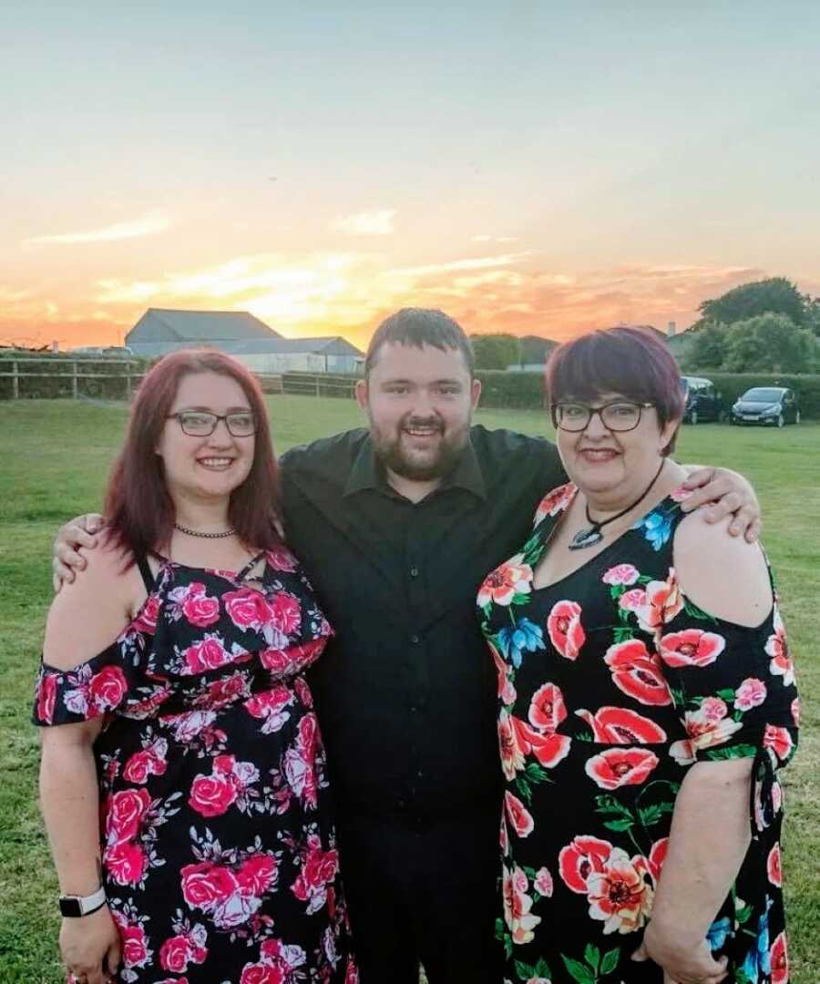 Woman with severe asthma and Crohn's disease takes a photo with her brother and mother with the sunset behind them