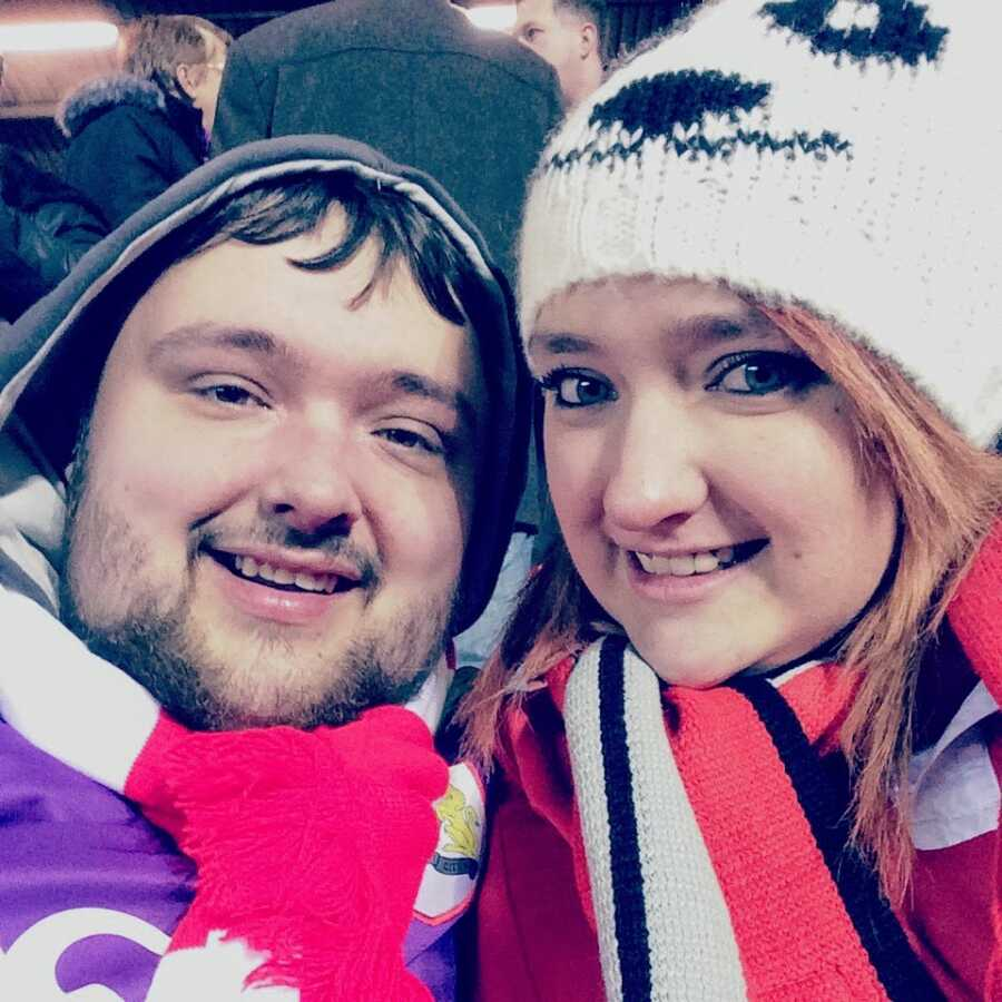 Brother and sister take a selfie together while bundled up in warm clothes as a sporting event