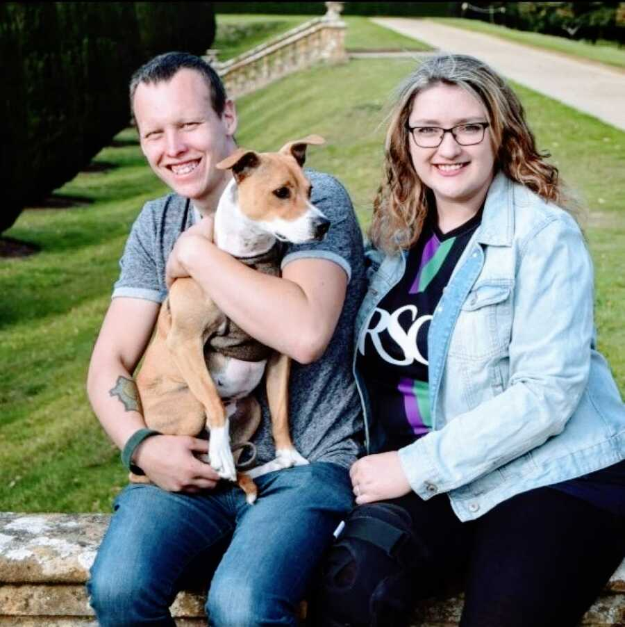 Woman with Woman with severe brittle asthma takes a family photo with her husband and their dog