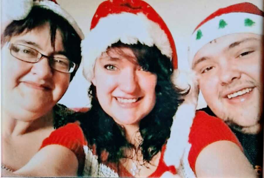 Teen girl takes a selfie with her mom and brother, who both have asthma, while wearing Santa hats