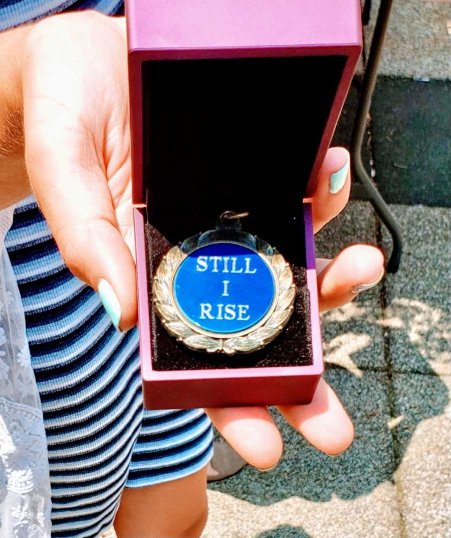 """Woman graduating from program that helped her overcome human trafficking takes photo of medal that says """"Still I Rise"""""""
