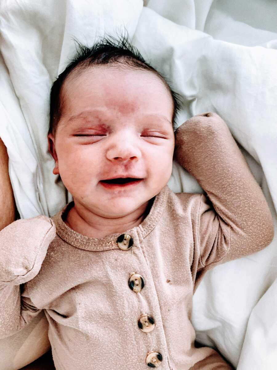 Newborn baby boy with a head full of dark hair in tan onesie smiles big in his sleep