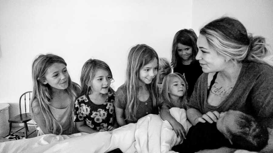 Mom to seven holds her newborn sons while her six daughters look at him with love and admiration