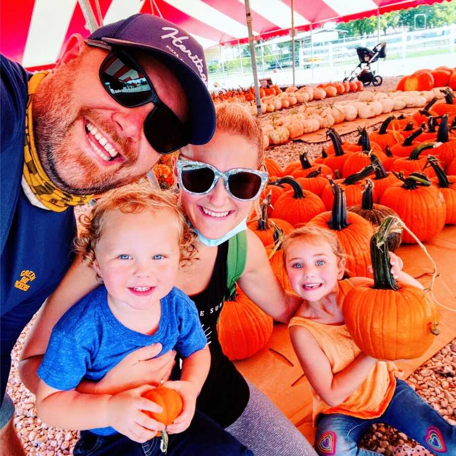 Young man dealing with mental health struggles smiles with his family at a pumpkin patch