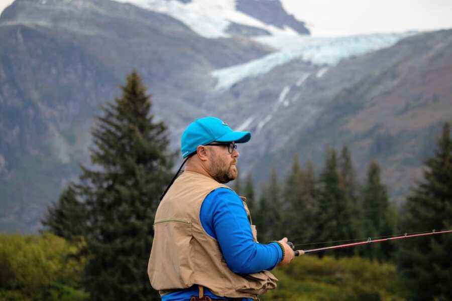Young man of faith working through mental health struggles takes a serious photo while fishing in a mountainous area