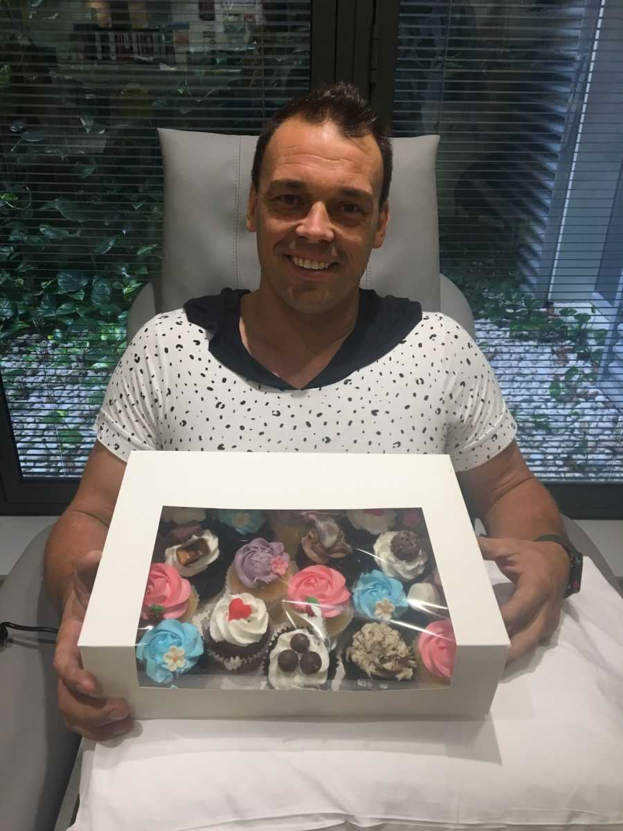 dad holding box of cupcakes