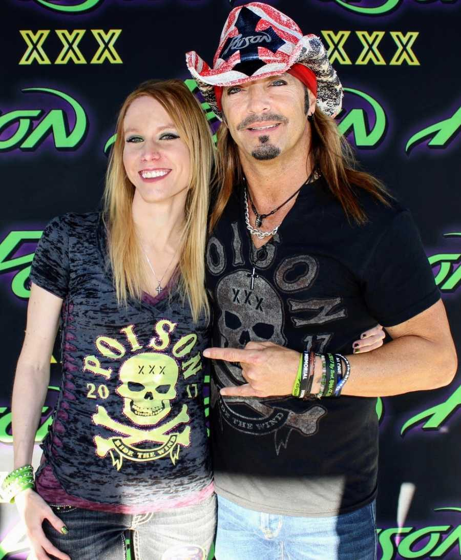 Woman who made hats for Bret Michaels takes a photo with him while they wear matching shirts and he wears her hat
