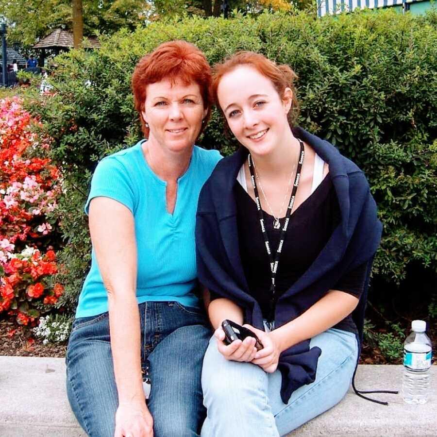 一个十几岁的女孩和她的妈妈坐在混凝土长凳上拍了张照片