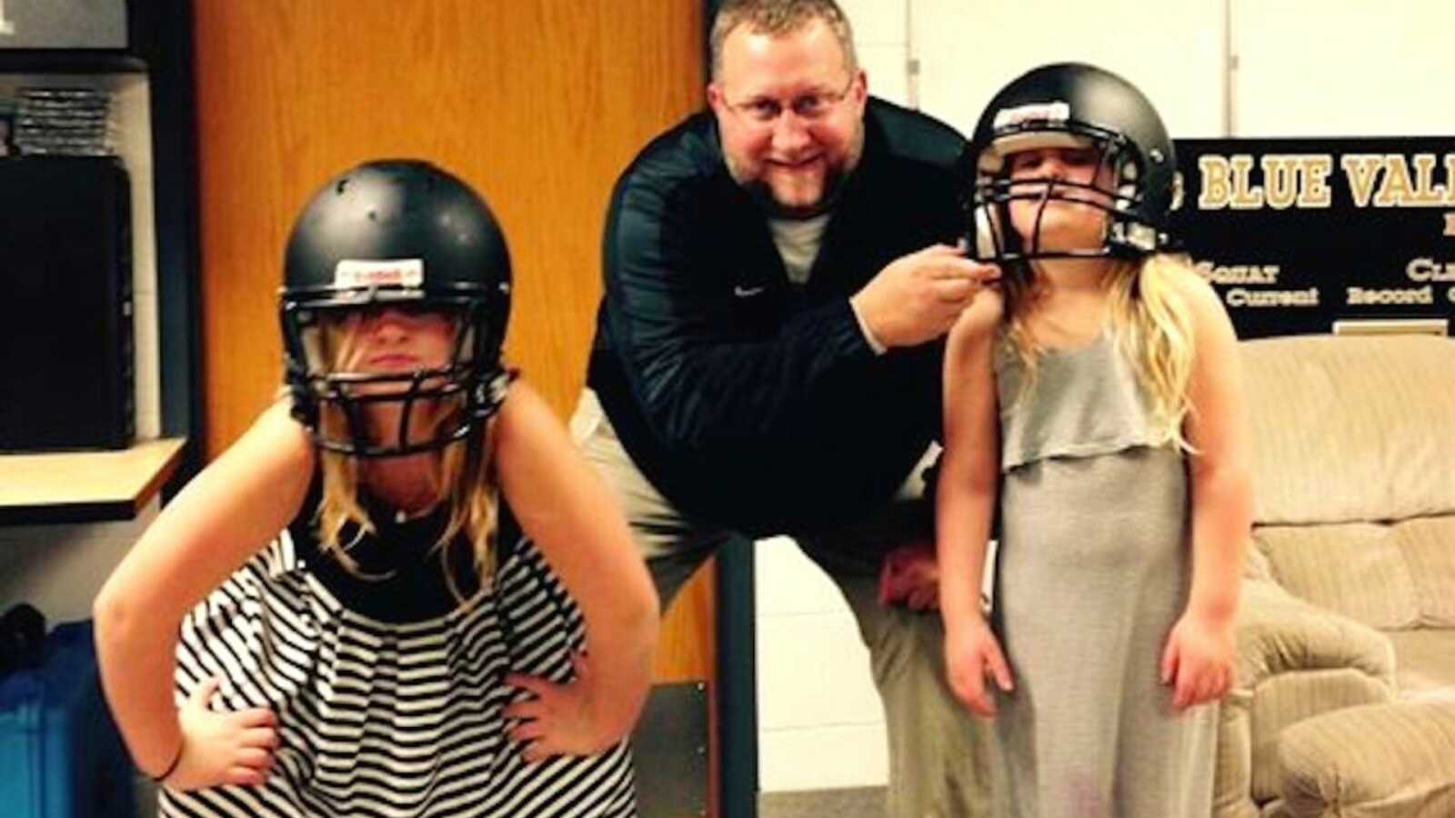 Father with two daughters being silly in football helmets