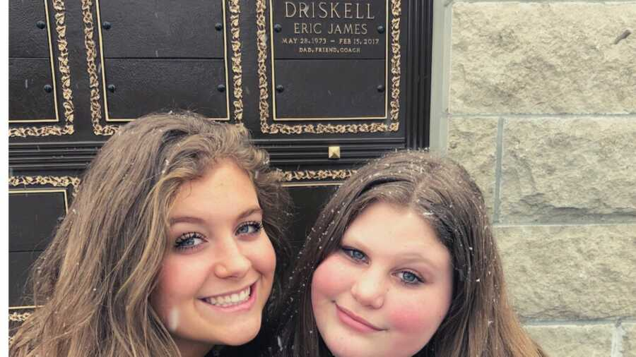 Two daughters smiling in front of father's grave