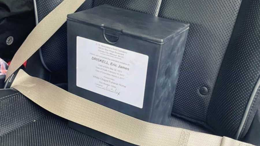 Box of ashes behind seat belt in black car