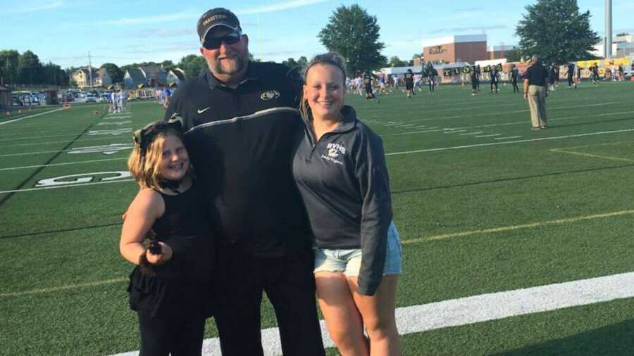 Football coach with his two daughters on football field