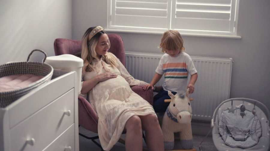 pregnant mom with son in nursery